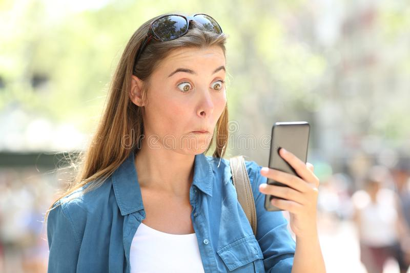 Astonished woman reading phone content in the street. Portrait of an astonished woman reading smart phone content in the street royalty free stock images
