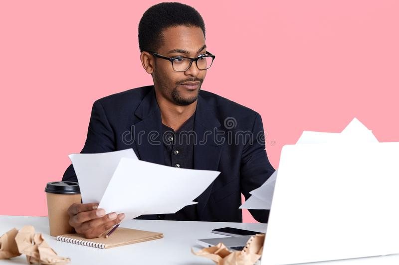 Astonished young black man, entrepreneur wears spectacles and black jacket, holds papers in hands, works freelance from home. royalty free stock photography