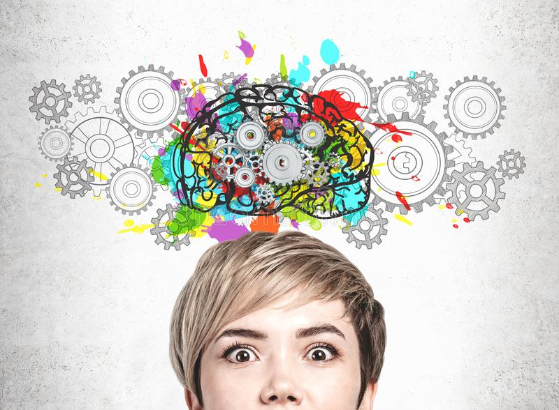 Astonished young woman, brainstorming concept. Head of astonished blonde young woman near concrete wall with colorful brain sketch with gears drawn on it royalty free stock photos