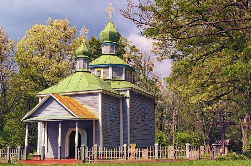 Astonishing  landscape view of ancient wooden cossack church with small cemetery in forest. Few minutes before spring thunderstorm stock photography