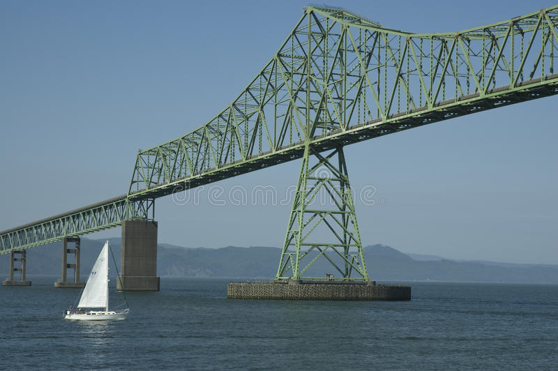 Astoria–Megler Bridge, Oregon. Sailboat going under the Astoria–Megler Bridge on the Columbia River in Oregon stock image