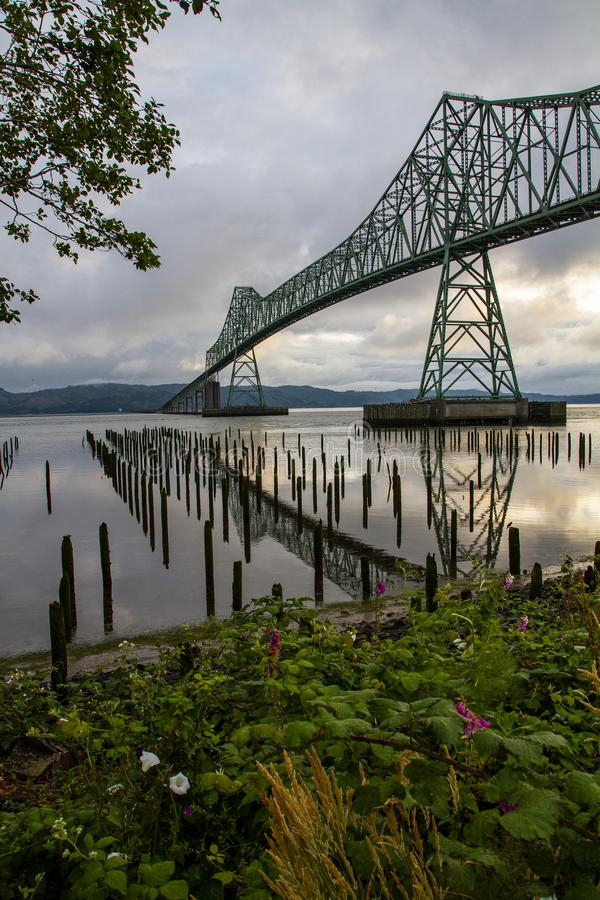 Astoria-Megler Bridge, Astoria, Oregon on an Early Overcast Morning. With darkened cloud cover and remnants of piers in the foreground royalty free stock photography