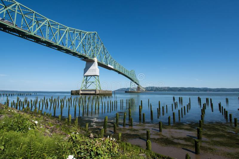 Astoria-Megler bridge, which goes over the Columbia River in Astoria Oregon. Dock pillars in foreground stock photo