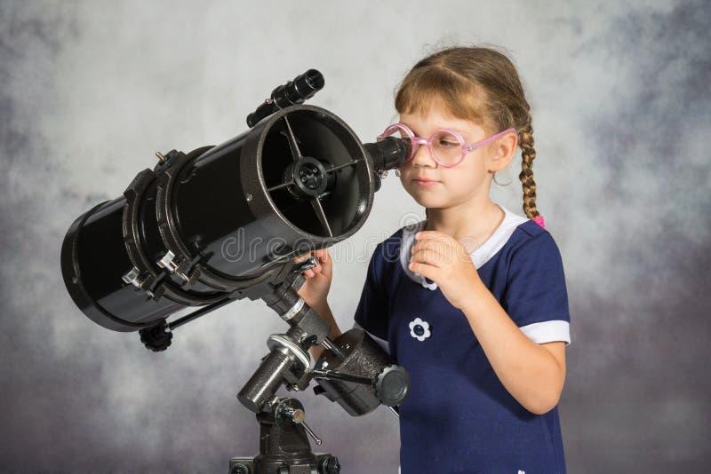 Astrônomo da menina surpreendido felizmente pelo que viu no telescópio fotografia de stock