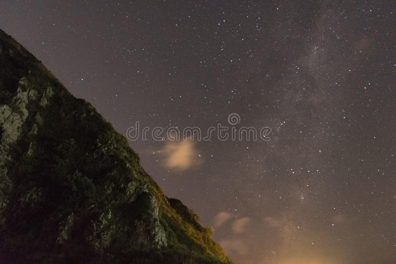 Astro Galaxy Star Cliff. Edge of cliff with rocky edges. Milkyway leading in other direction, soft clouds beneath royalty free stock image