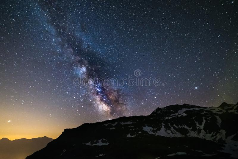 Astro night sky, Milky way galaxy stars over the Alps, Mars and Jupiter planet, snowcapped mountain range.  royalty free stock images