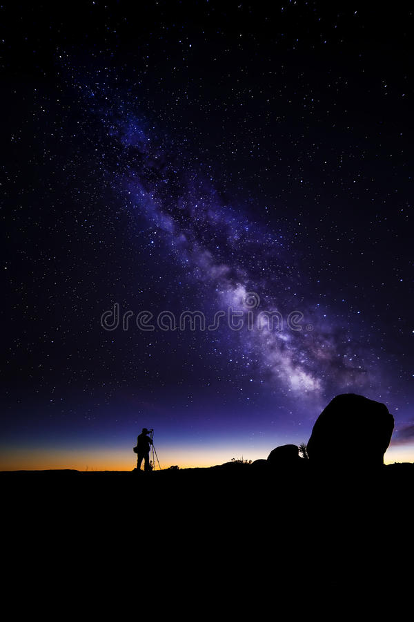 Astro Photographer in the desert and view of Milky Way Galaxy. Photographer doing astro photography in a desert nightscape with milky way galaxy. The background stock images