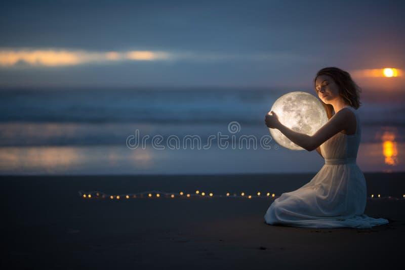 Astrología Secreto y enigma Hermosa chica atractiva en una playa nocturna con arena abraza la luna, foto de arte imagenes de archivo