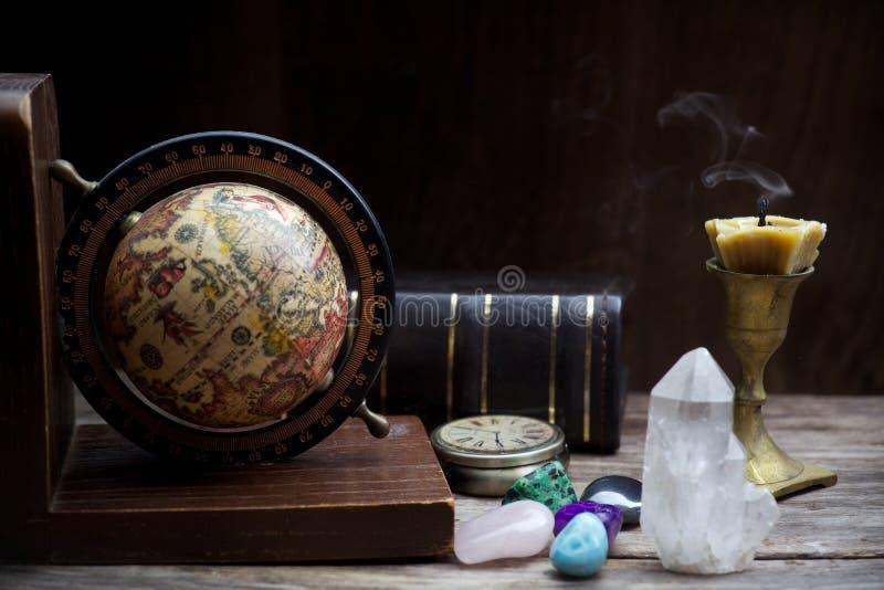 Astrologia antica Vecchi globo e libri di astrologia con la candela fotografia stock