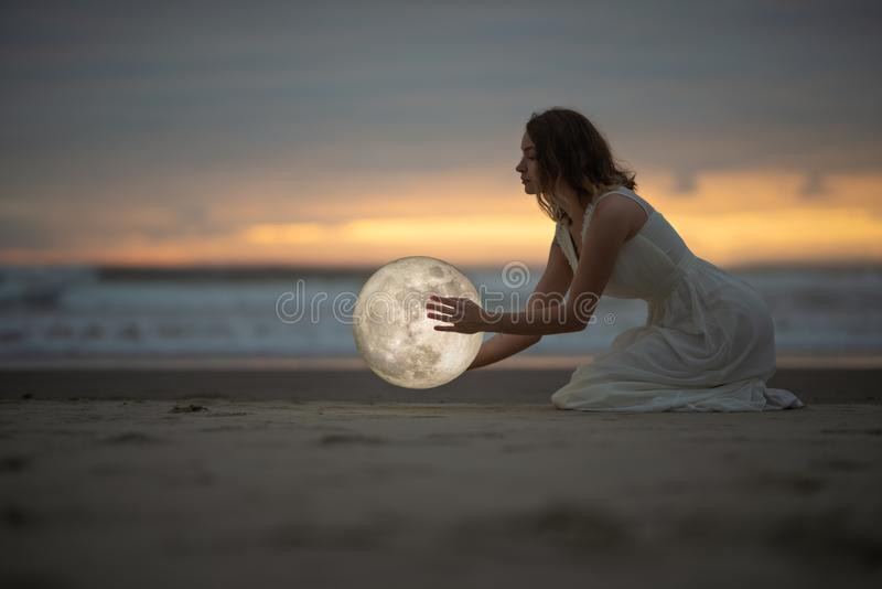 Astrologia Segreto e indovinello Bellissima ragazza su una spiaggia notturna con la sabbia abbraccia la luna, foto d'arte fotografia stock