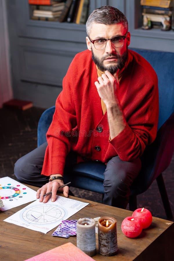 Astrologist de ojos oscuros que lleva la rebeca roja que se sienta en la tabla con las velas foto de archivo