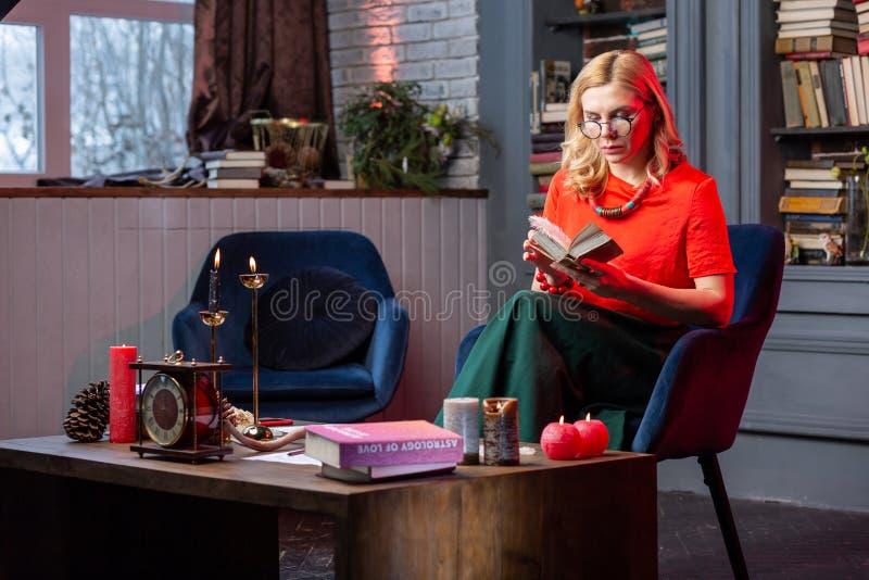 Astrologist esperto que senta-se na sala de visitas e que lê o livro da astrologia fotografia de stock royalty free