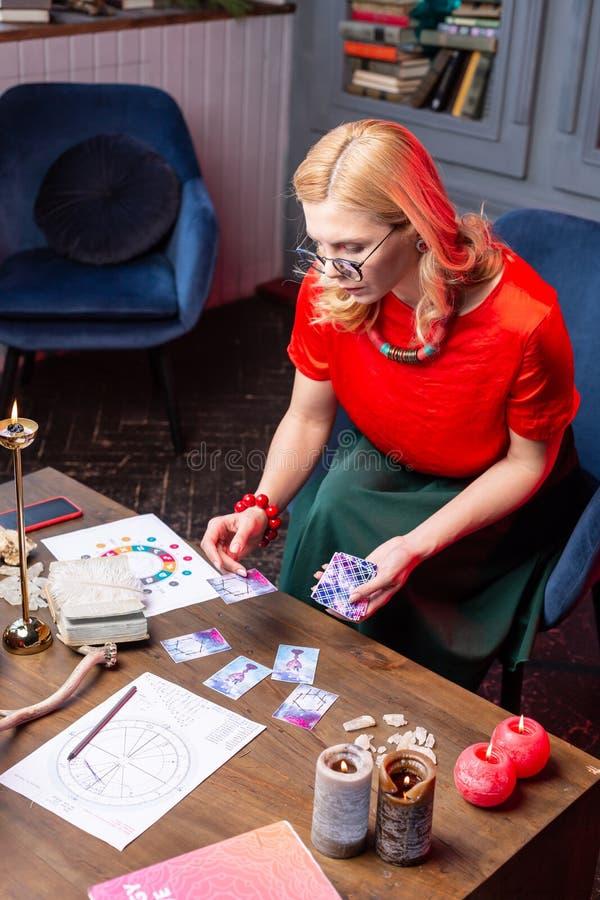 Astrologist maduro que se sienta en butaca y la predicción futura practicante imagenes de archivo