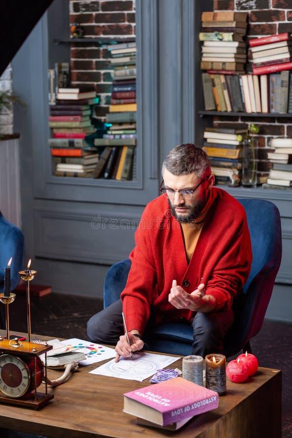 Astrologist que se sienta en la tabla con las velas que estudian nueva práctica imagen de archivo
