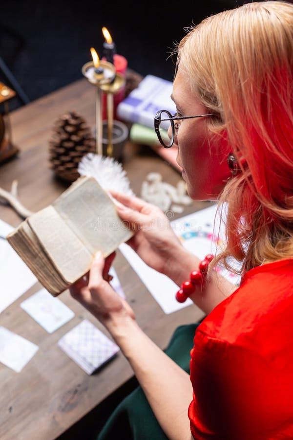 astrologist Rubio-cabelludo que lleva el libro viejo del mago de la lectura roja de la pulsera fotos de archivo
