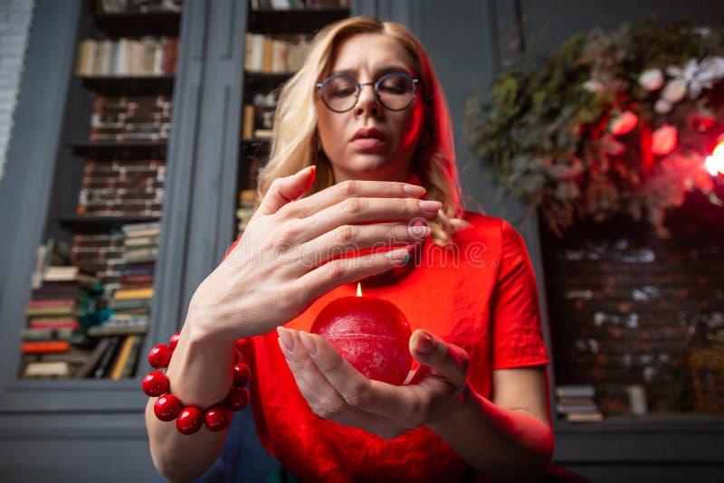 Astrologist rubio que lleva la pulsera masiva que lleva a cabo la vela ardiendo fotografía de archivo