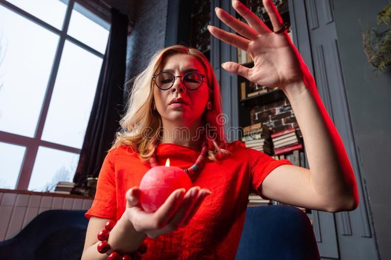 Astrologist wearing necklace and bracelet practicing future prediction. Blonde-haired astrologist. Blonde-haired astrologist wearing nice necklace and bracelet stock photos