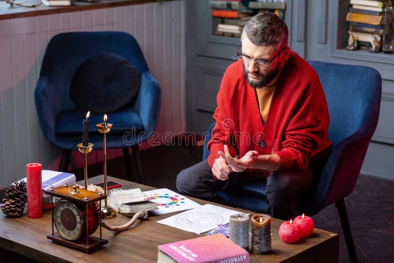 Astrologue barbu s'asseyant dans le livre de lecture de fauteuil et faisant la pratique images libres de droits