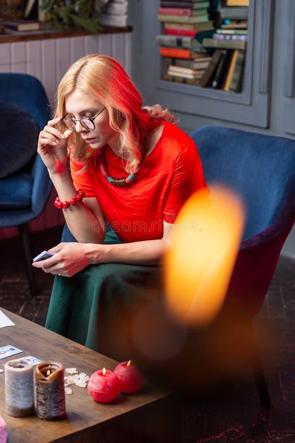 Astrologue blond féminin s'asseyant à la table avec les bougies brûlantes photos stock