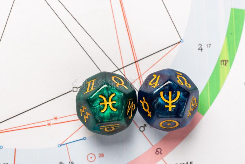 Astrology Dice with zodiac symbol of Pisces Feb 19 - Mar 20 and its ruling planet Neptune. On Natal Chart Background royalty free stock photo