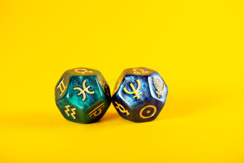 Astrology Dice with zodiac symbol of Pisces Feb 19 - Mar 20 and its ruling planet Neptune. On Yellow Background royalty free stock image