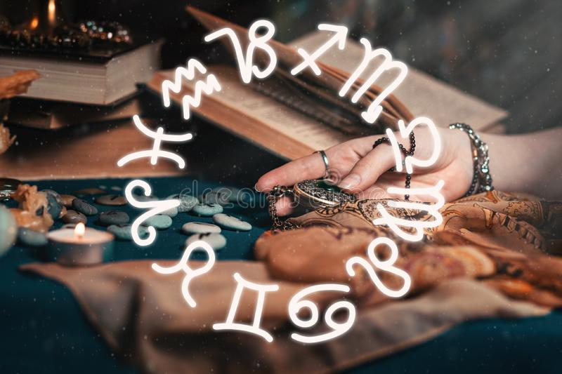 Astrology and esotericism. The female hand of the sorceress holds an amulet in her hands. In the background, old books, fortune- royalty free stock photo