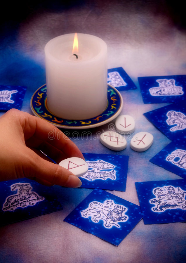 Astrology and runes. Esoterism concept with runes astrological cards and candle royalty free stock photography
