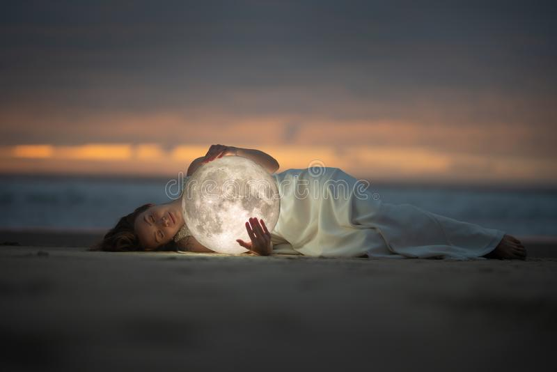 Astrology. Secret and riddle. Beautiful attractive girl on a night beach with sand hugs the moon, art photo stock photography