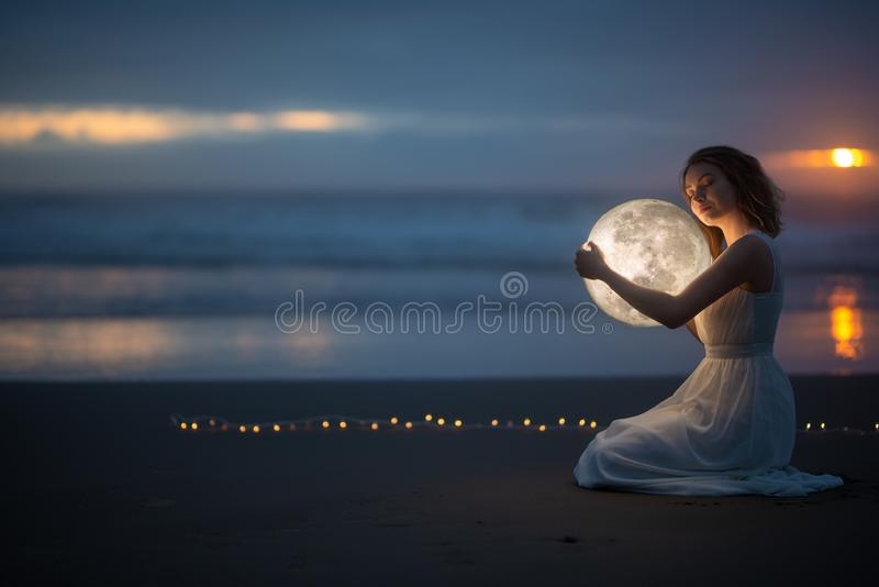 Astrology. Secret and riddle. Beautiful attractive girl on a night beach with sand hugs the moon, art photo.  stock images