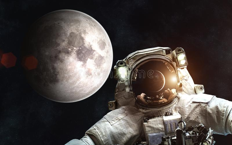 Astronaut on background of Moon. Sun and Earth in reflection of helmet of spacesuit. Elements of the image are furnished by NASA stock photo