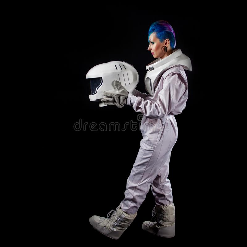 Astronaut on a black background, a young woman with face art in the space suit. Go ahead stock photo