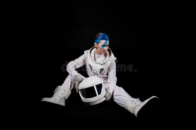 Astronaut on a black background, a young woman with face art in the space suit. Sits royalty free stock images