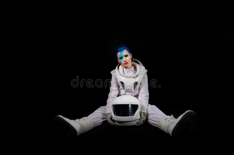 Astronaut on a black background, a young woman with face art in the space suit. Sits stock images