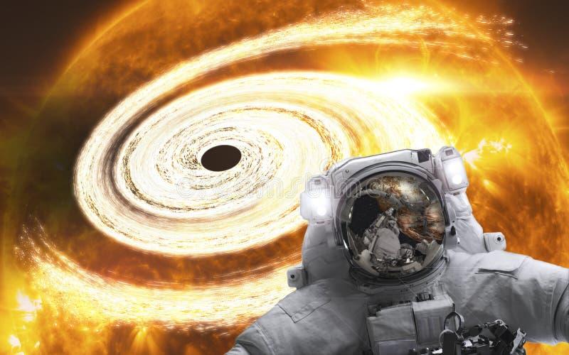 Astronaut in de ruimte met oranje reuze zwart erachter gat Elementen van dit die beeld door NASA wordt geleverd royalty-vrije stock foto's