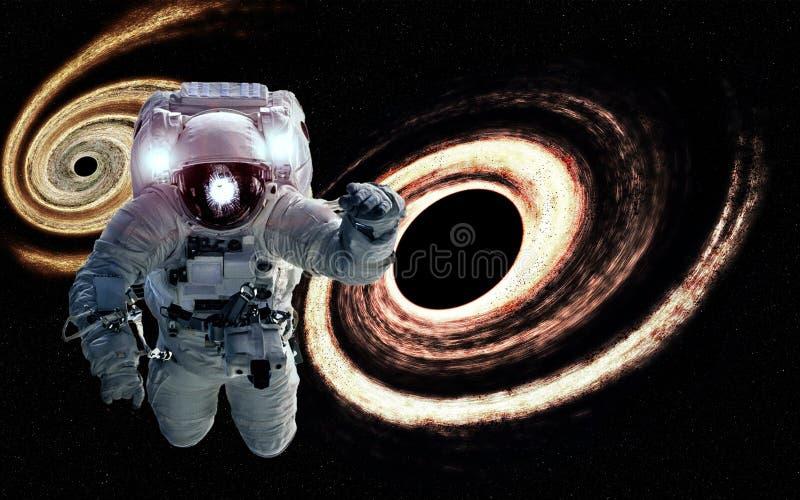 Astronaut in de ruimte met oranje reuze zwarte erachter gaten Elementen van dit die beeld door NASA wordt geleverd stock foto