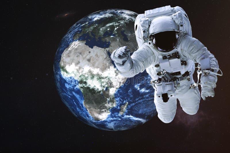 Astronaut dichtbij de Aardeplaneet stock afbeeldingen