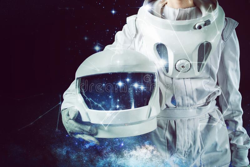 Astronaut in een helm van de spacesuitholding in zijn hand Close-up, gemengde media stock fotografie