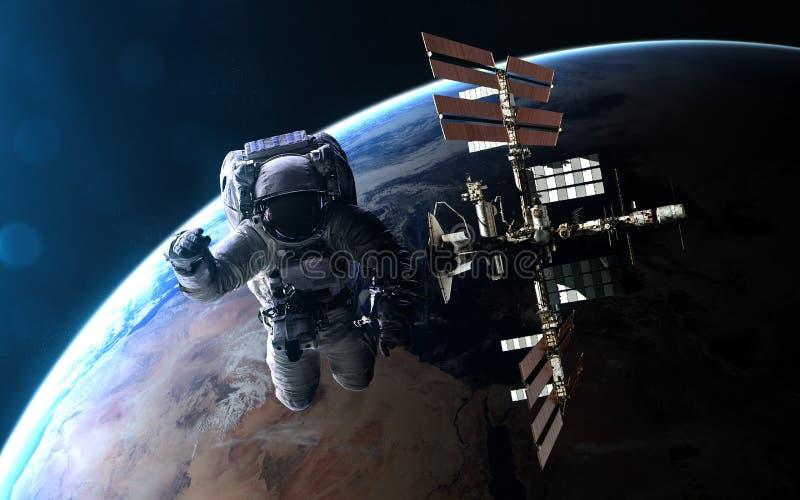 Astronaut en ISS op achtergrond van Aarde in blauwe stralen van Zon De elementen van het beeld worden geleverd door NASA royalty-vrije stock afbeelding