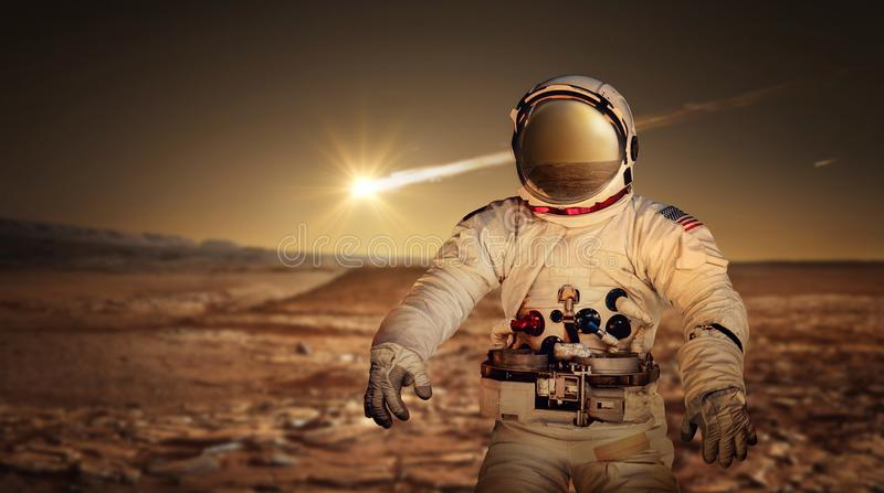 Astronaut exploring the surface of red planet Mars. royalty free stock image