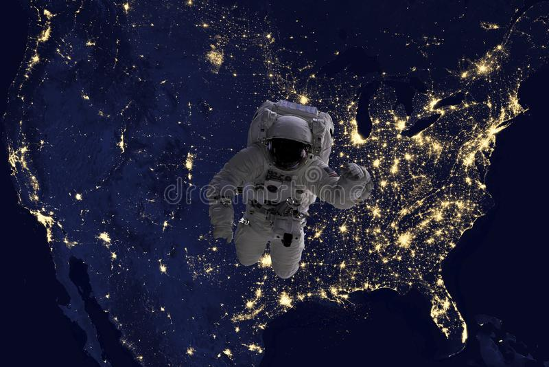 Astronaut flying in open space over the USA during night, near earth. Image made of NASA photos f. Astronaut flying in open space over the USA during night, near stock image