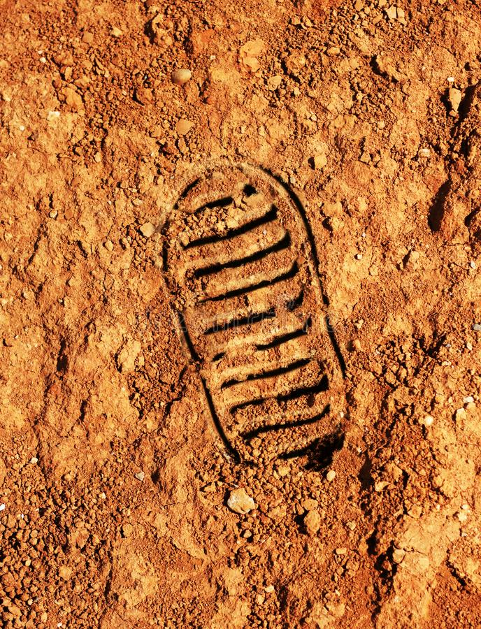 Astronaut footprint on red Martian soil stock images