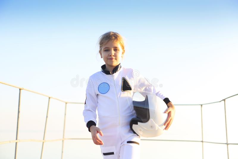 Astronaut futuristic kid girl with white full length uniform and helmet wearing silver shoes outdoors stock photo
