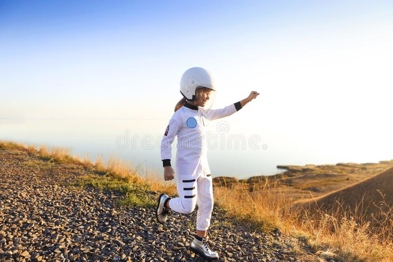 Astronaut futuristic kid girl with white full length uniform and helmet wearing silver shoes outdoors stock images