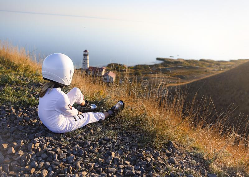 Astronaut futuristic kid girl with white full length uniform and helmet wearing silver shoes outdoors royalty free stock photos