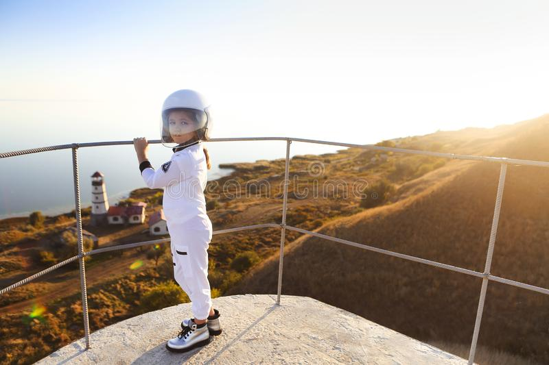 Astronaut futuristic kid girl with white full length uniform and helmet wearing silver shoes outdoors stock photography