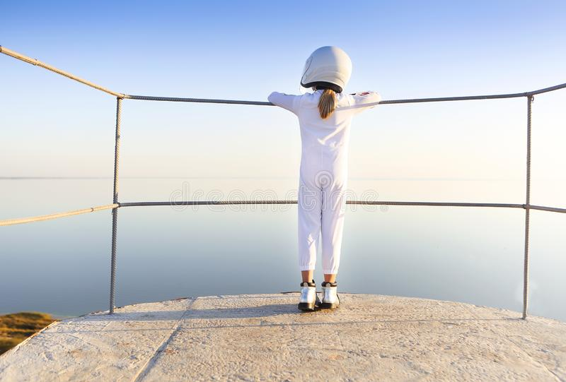 Astronaut futuristic kid girl with white full length uniform and helmet wearing silver shoes outdoors stock image