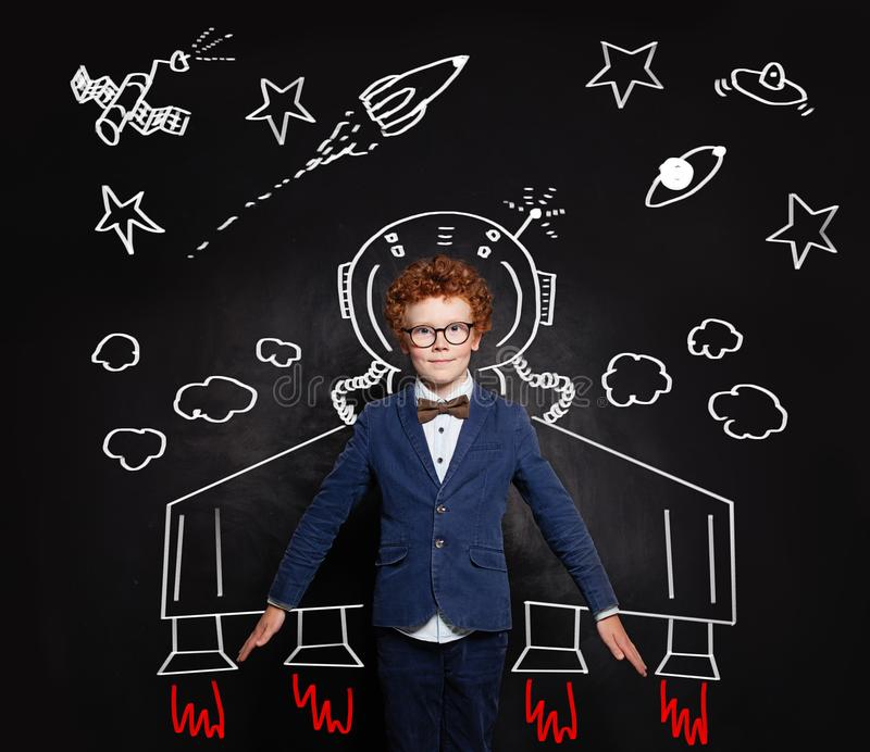 Astronaut kid. Smart child boy spaceman on blackboard background with space pattern royalty free stock photo