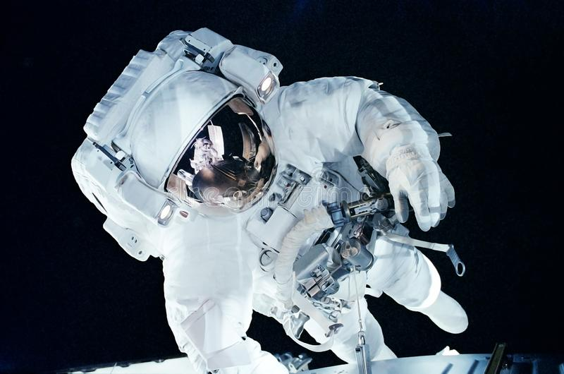 Astronaut in open dark space. Elements of this image were furnished by NASA stock photo