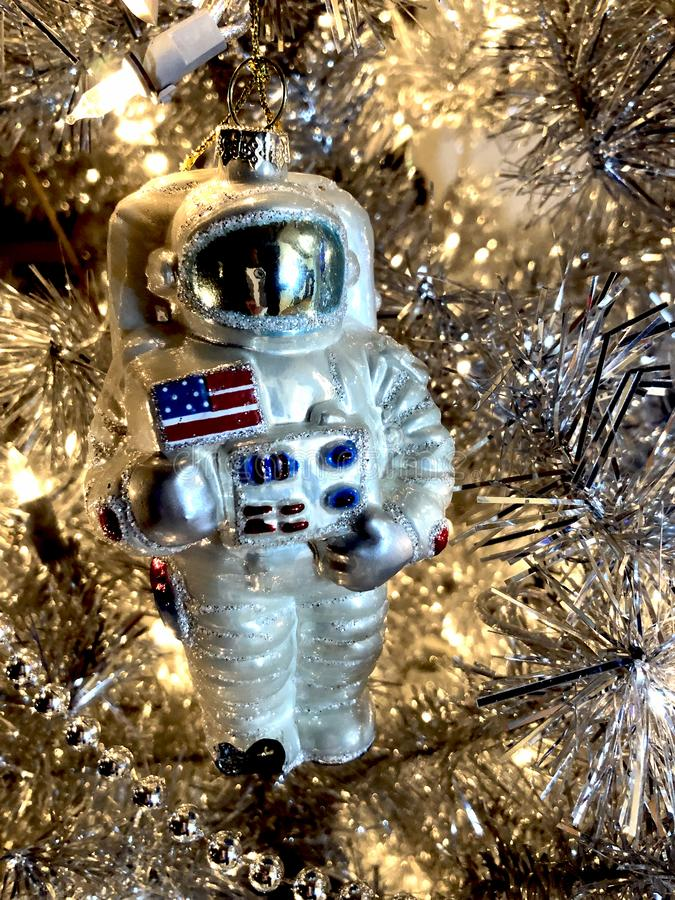 Astronaut ornament celebrates moon landing. Apollo astronaut glass ornament waves an American flag in recognition of moon landing. This year, 2019 is the stock photo