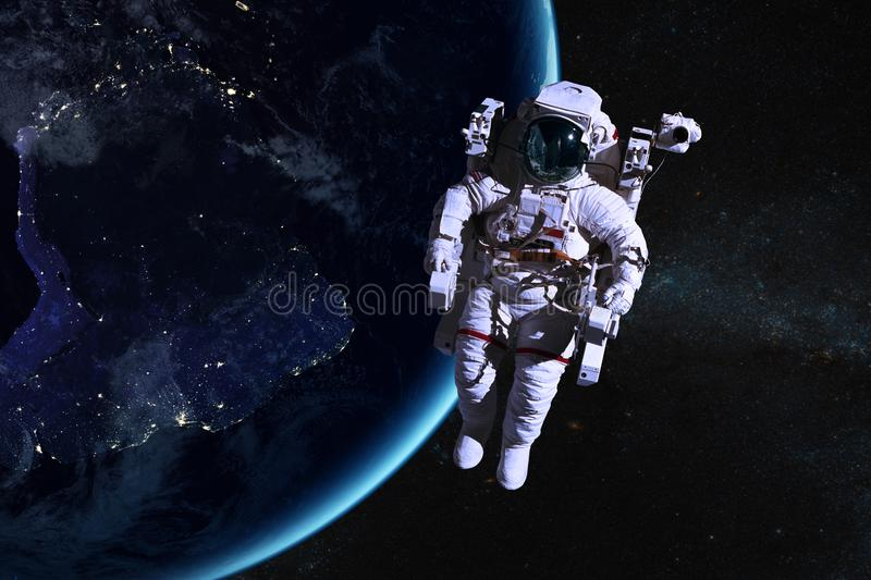 Astronaut in outer space on background of the night Earth. Elements of this image furnished by NASA stock images